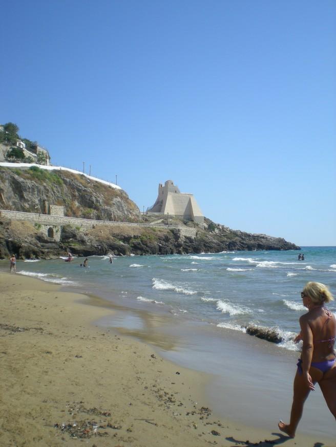 An Italian woman strolling the beach in Sperlonga